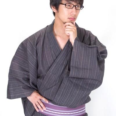 考え髭を触る浴衣メガネ男子の写真