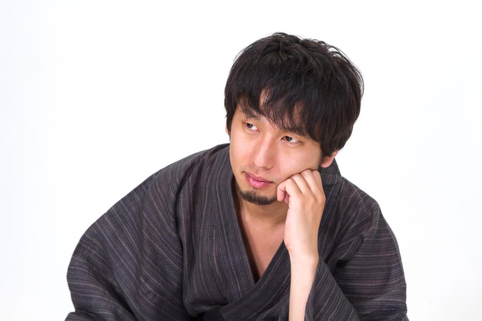 「肘立てて考える浴衣の男性」の写真[モデル:大川竜弥]