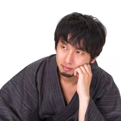 肘立てて考える浴衣の男性の写真