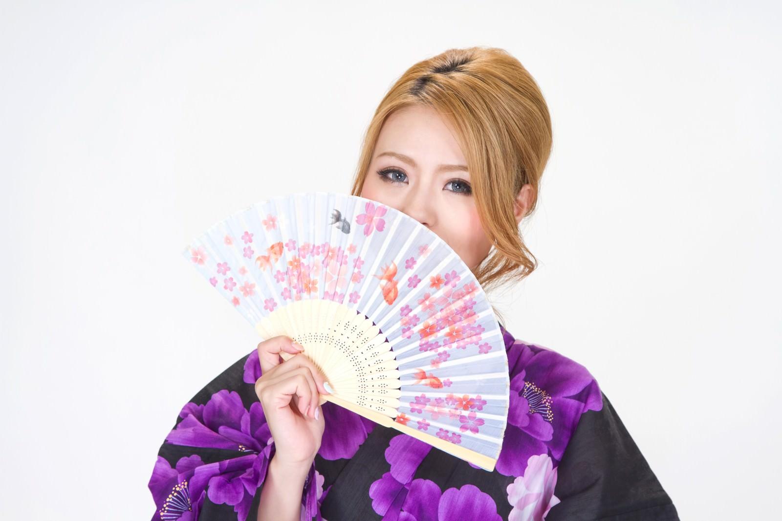 「金魚の扇子を広げる浴衣の女性」の写真[モデル:吉川明奈]