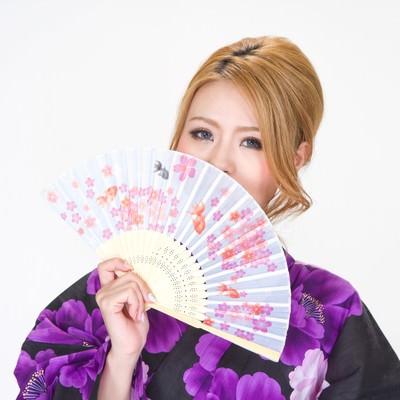 金魚の扇子を広げる浴衣の女性の写真