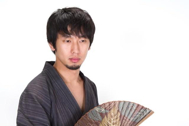 扇子を持ち虚ろげな表情の浴衣の男性の写真