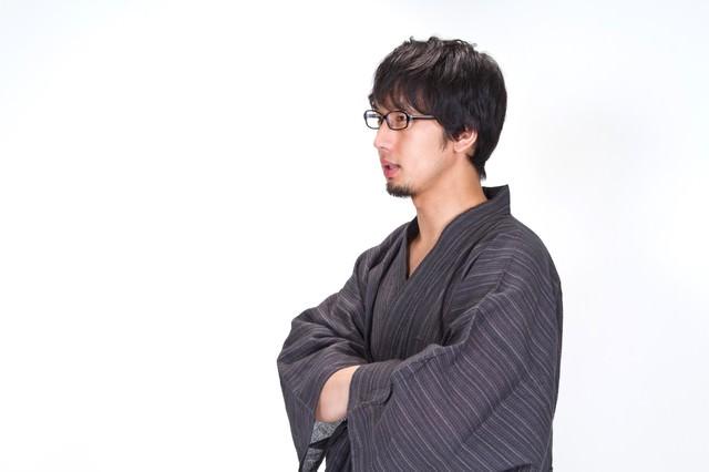 浴衣の袖に手を入れ横を向く男性の写真