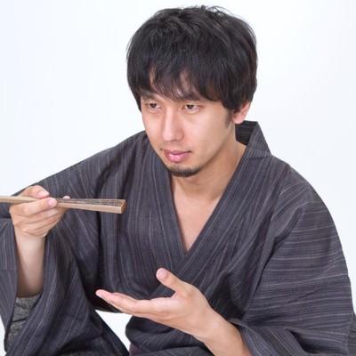 扇子を使って何かを食べる浴衣男子の写真
