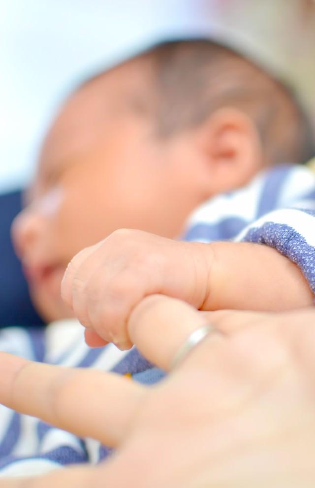 母親の指を握る赤ちゃんの写真