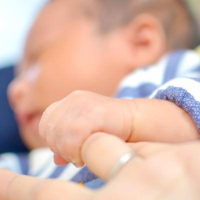 「母親の指を握る赤ちゃん」の写真素材