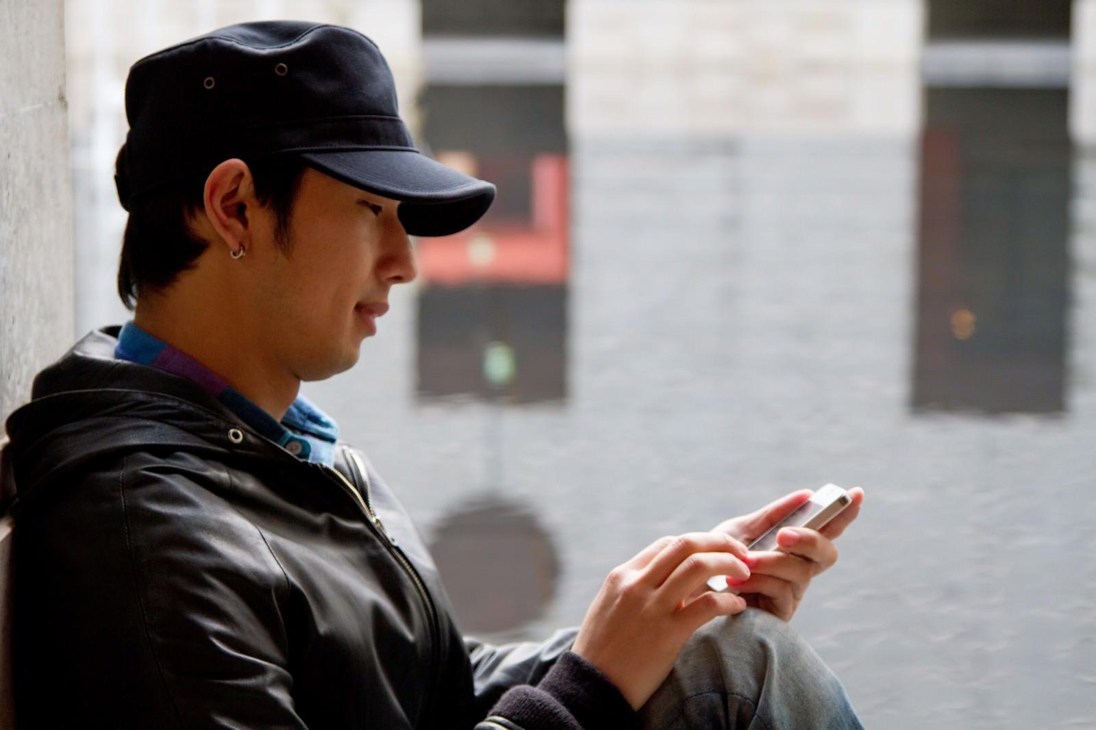 「スマホを操作する帽子の男性」の写真[モデル:大川竜弥]