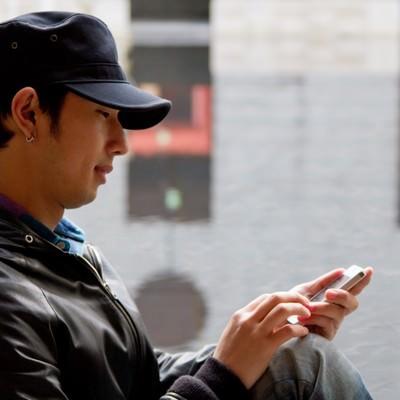 「スマホを操作する帽子の男性」の写真素材