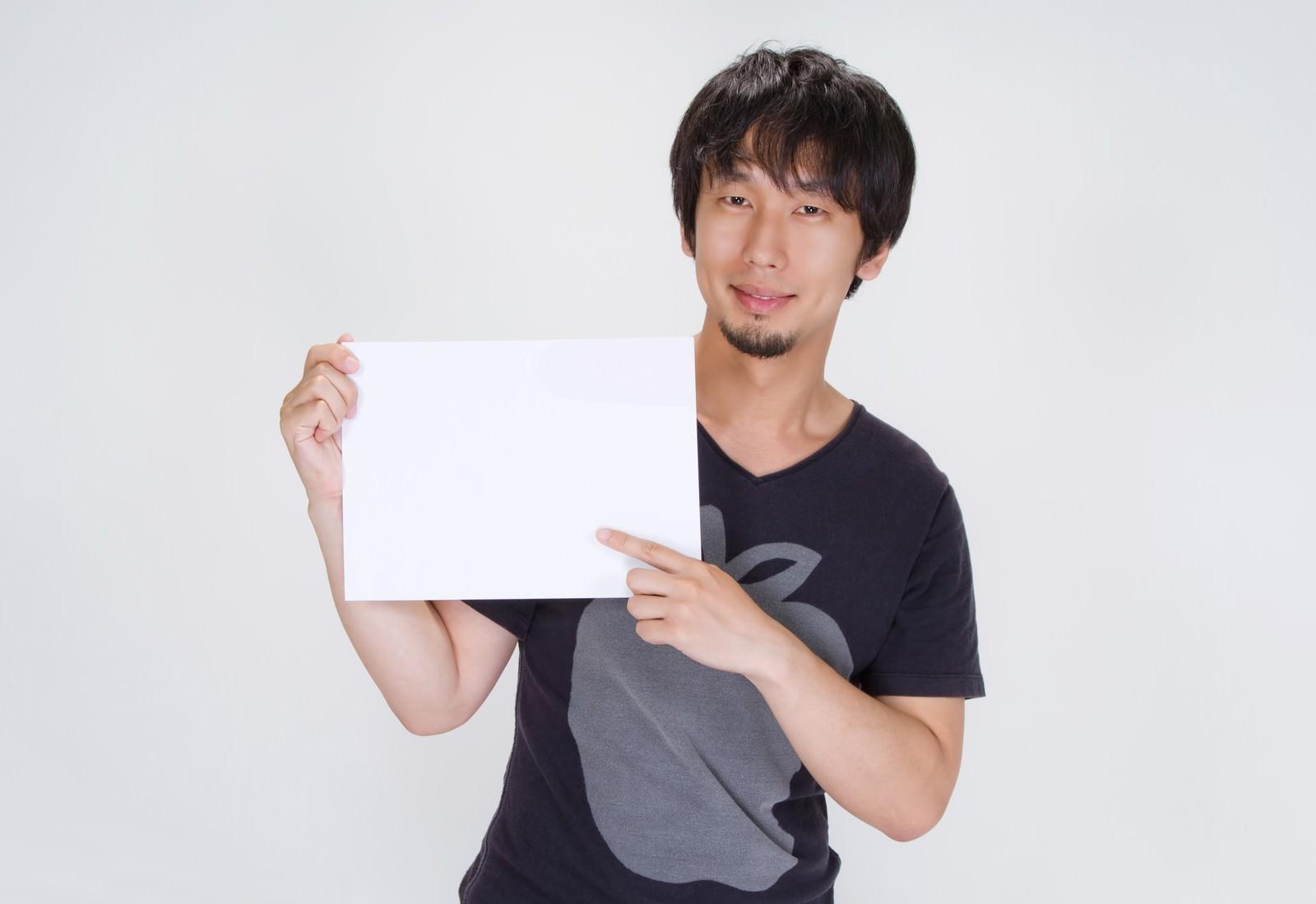 「ご案内の白いボードを持つ男性」の写真[モデル:大川竜弥]