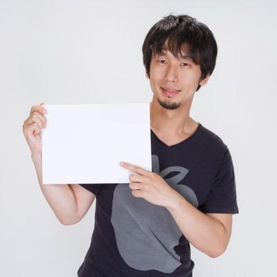 「ご案内の白いボードを持つ男性」の写真素材