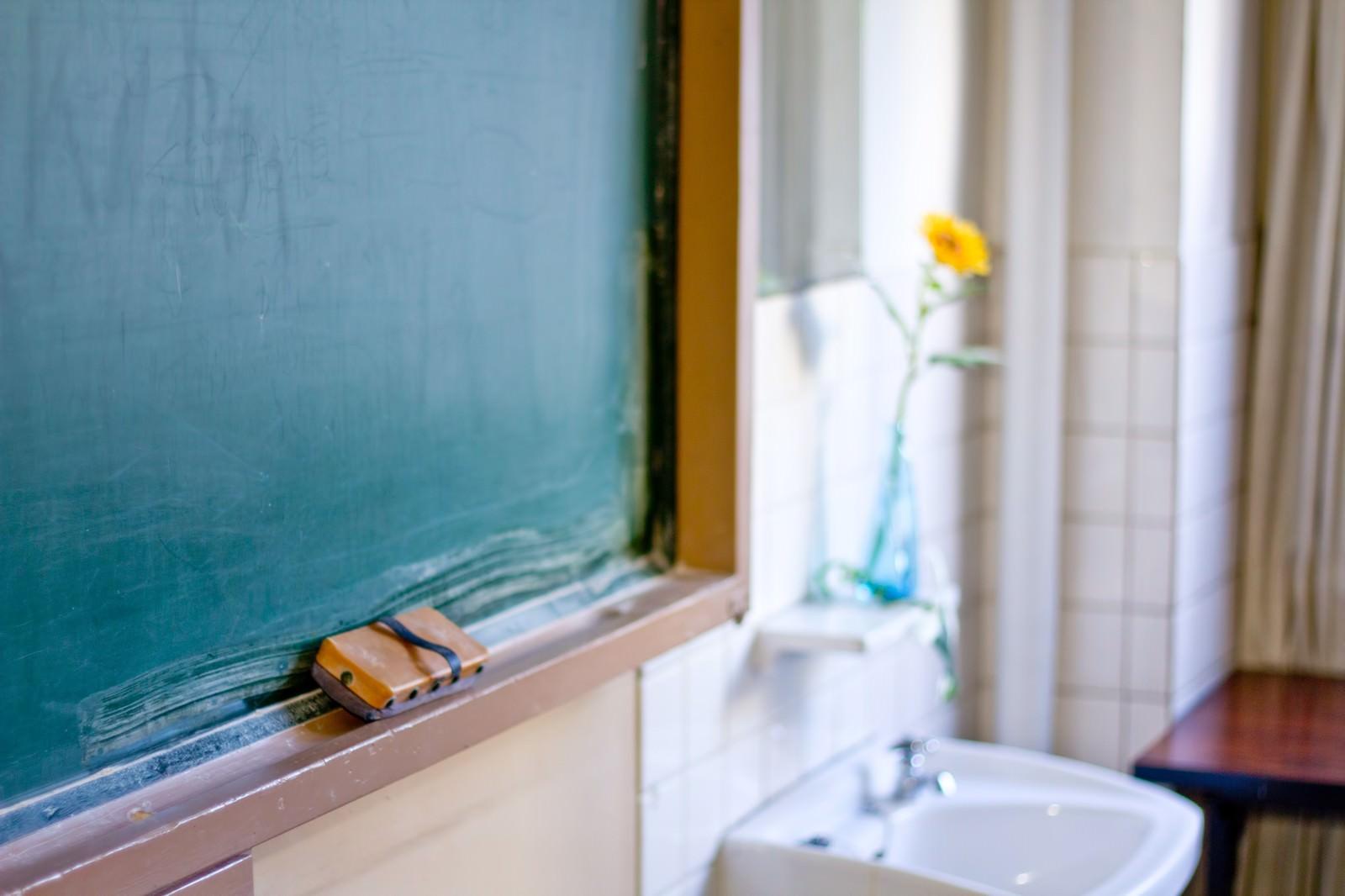 「教室の黒板と花瓶のお花」の写真