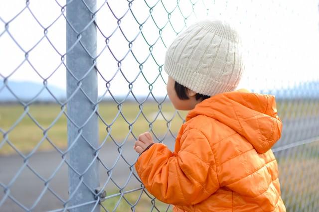 金網にしがみつく子供の写真