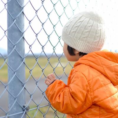 「金網にしがみつく子供」の写真素材