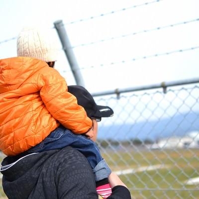 「フェンスと肩車をした親子」の写真素材