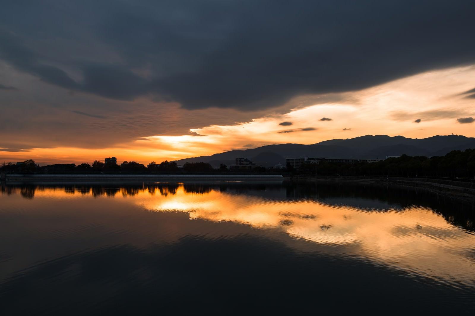 「夕焼けと反射する水面」の写真