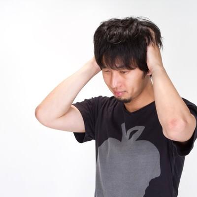 「悩み、頭をかきむしる男性」の写真素材