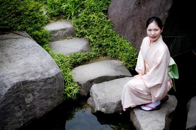 池の踏石にしゃがみこむ着物の女性の写真
