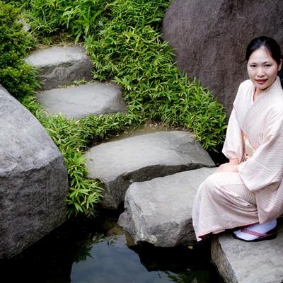 「池の踏石にしゃがみこむ着物の女性」の写真素材
