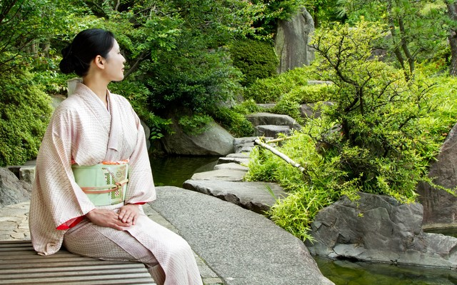 庭のベンチに座る着物の女性の写真