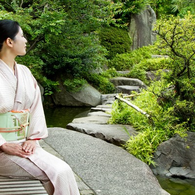 「庭のベンチに座る着物の女性」の写真素材