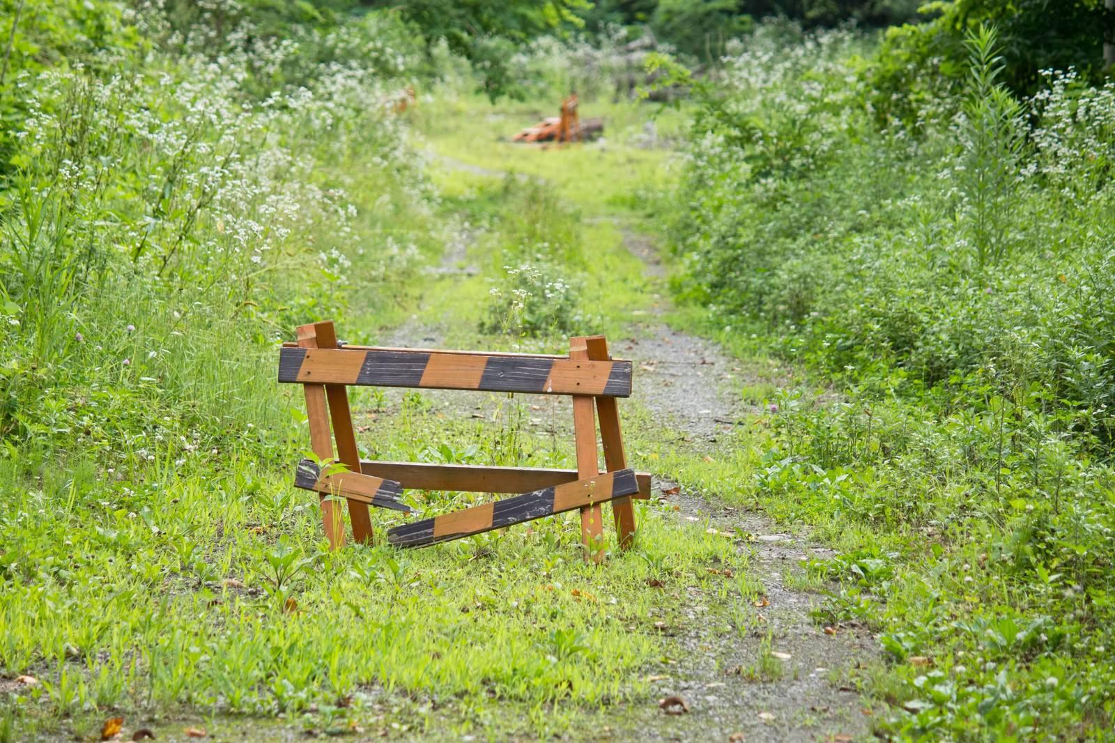 「壊れた通行止めと山道」の写真