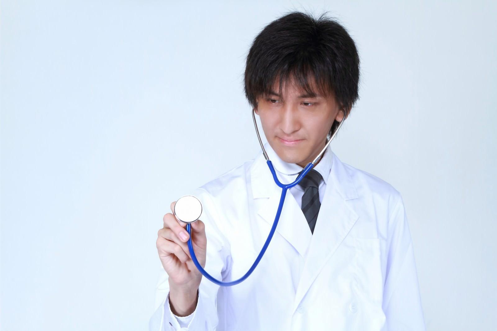 「聴診器を使う医師」の写真[モデル:ACE]