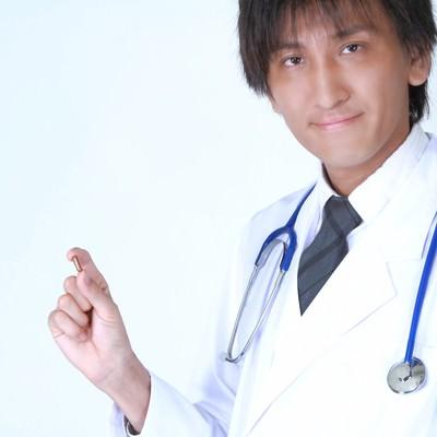 「カプセルを持った白衣の医師」の写真素材