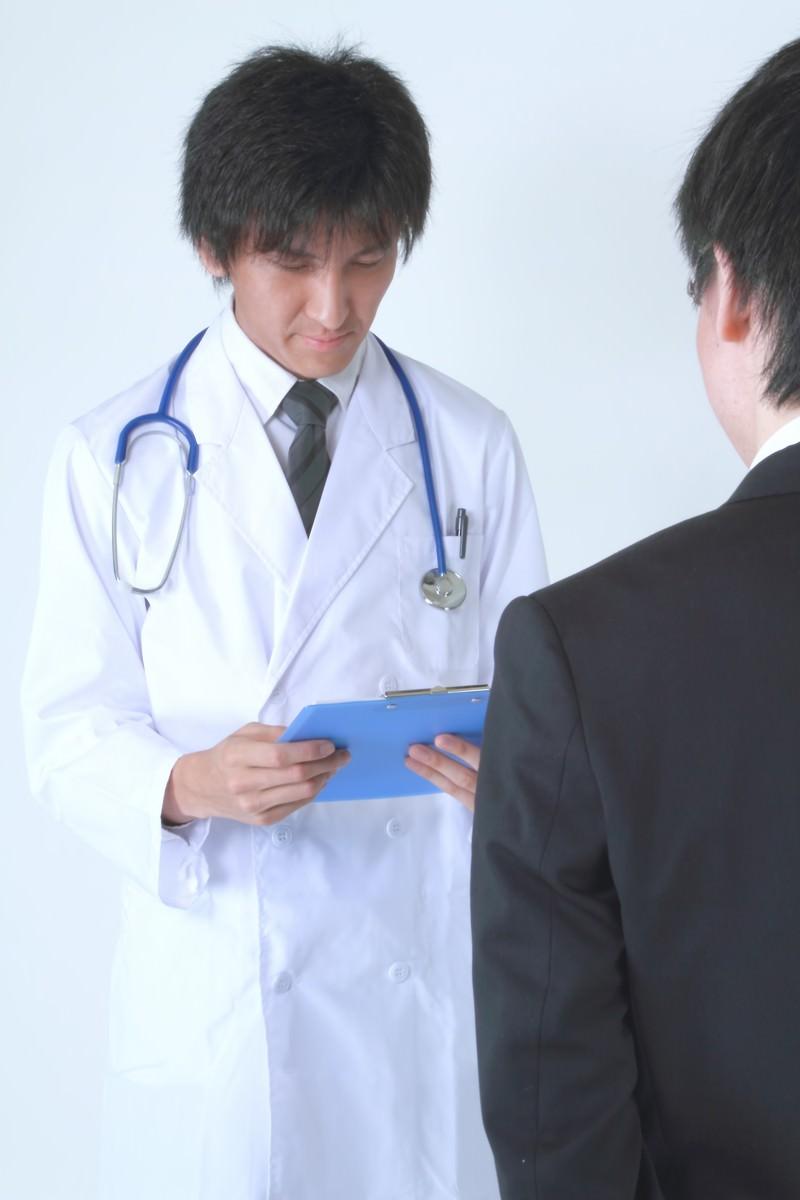 「カルテを再確認する担当医」の写真[モデル:ACE]