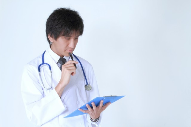 カルテを見て考えるドクターの写真