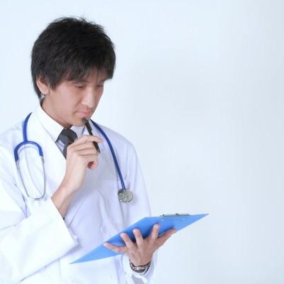 「カルテを見て考えるドクター」の写真素材