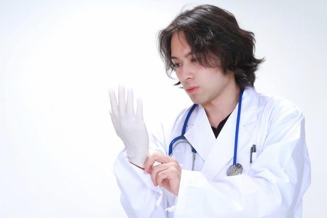 ゴム手袋を装着する若い医師の写真