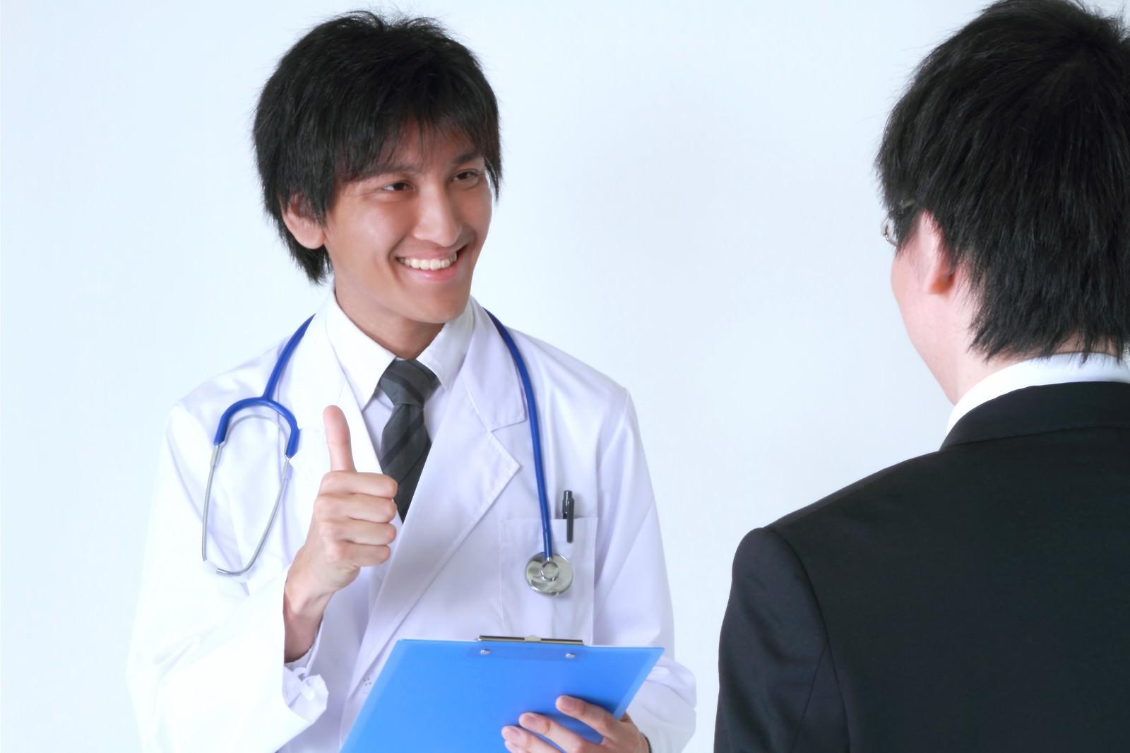 「サラリーマンに笑顔で診断結果を話す医者」の写真[モデル:ACE]