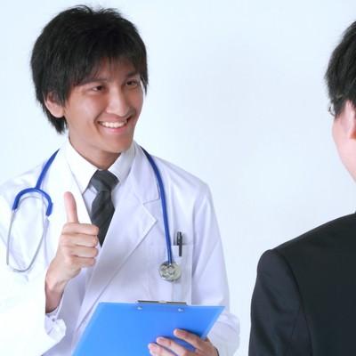 「サラリーマンに笑顔で診断結果を話す医者」の写真素材