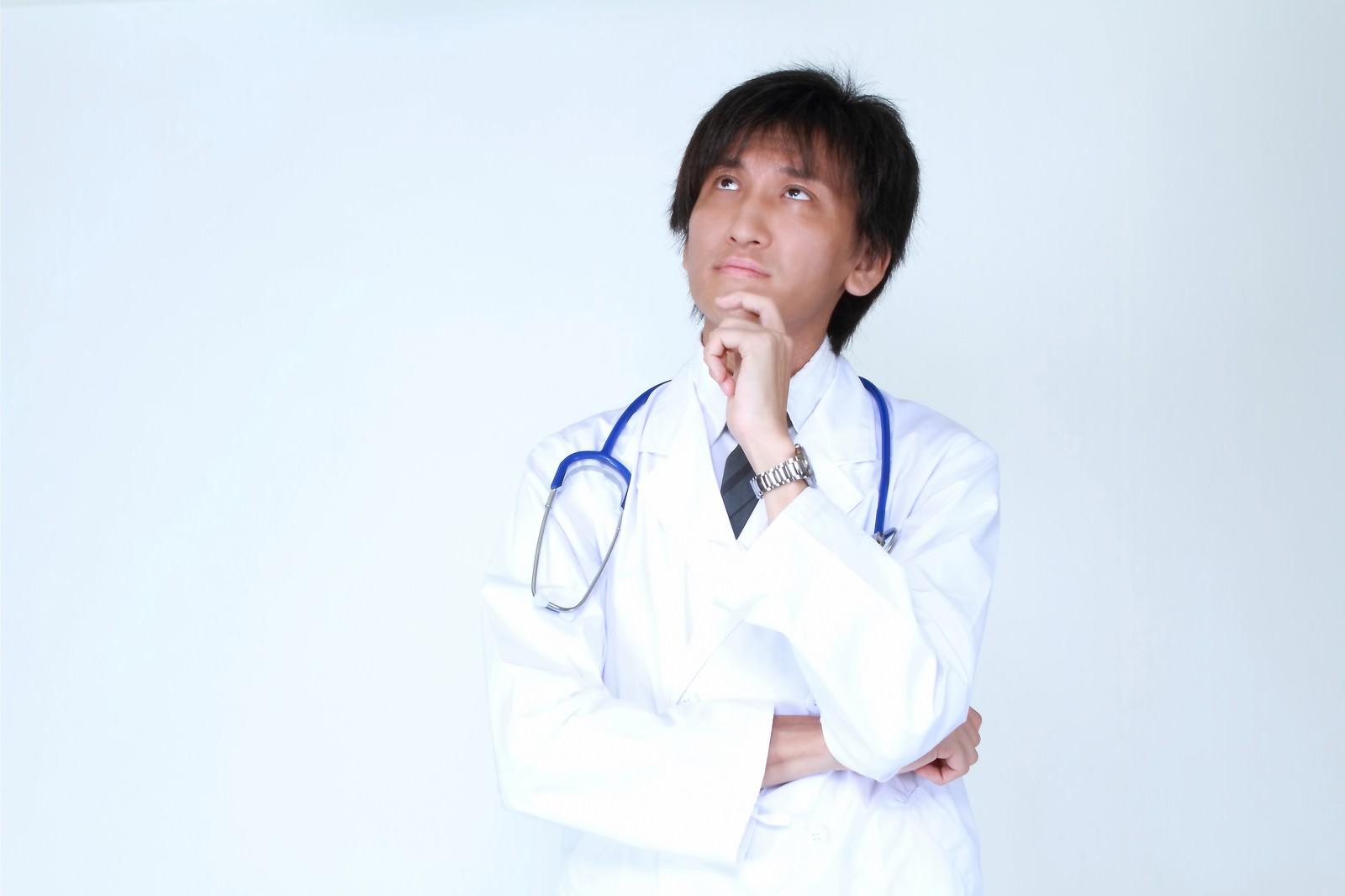 「天井を見上げ考える白衣のドクター」の写真[モデル:ACE]