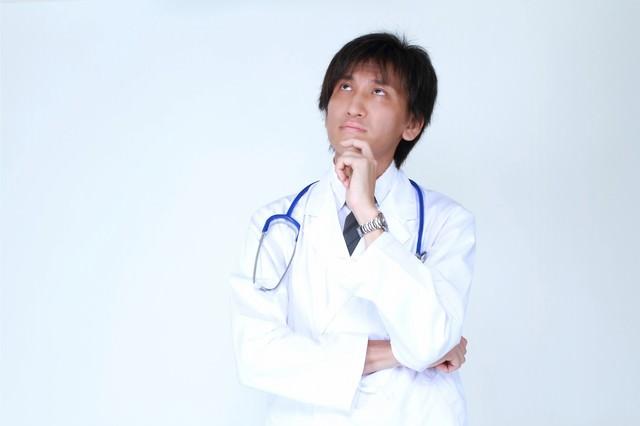 天井を見上げ考える白衣のドクターの写真