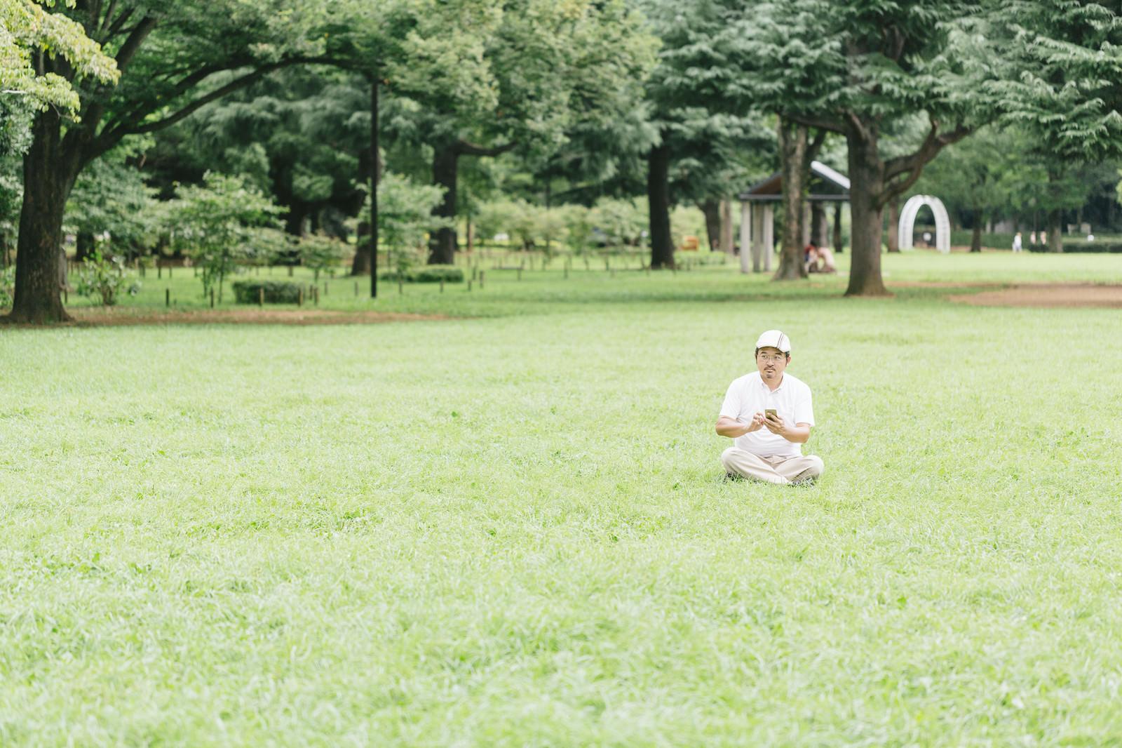 「息抜きに芝の上でスマホゲームをプレイ」の写真