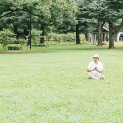 「息抜きに芝の上でスマホゲームをプレイ」の写真素材