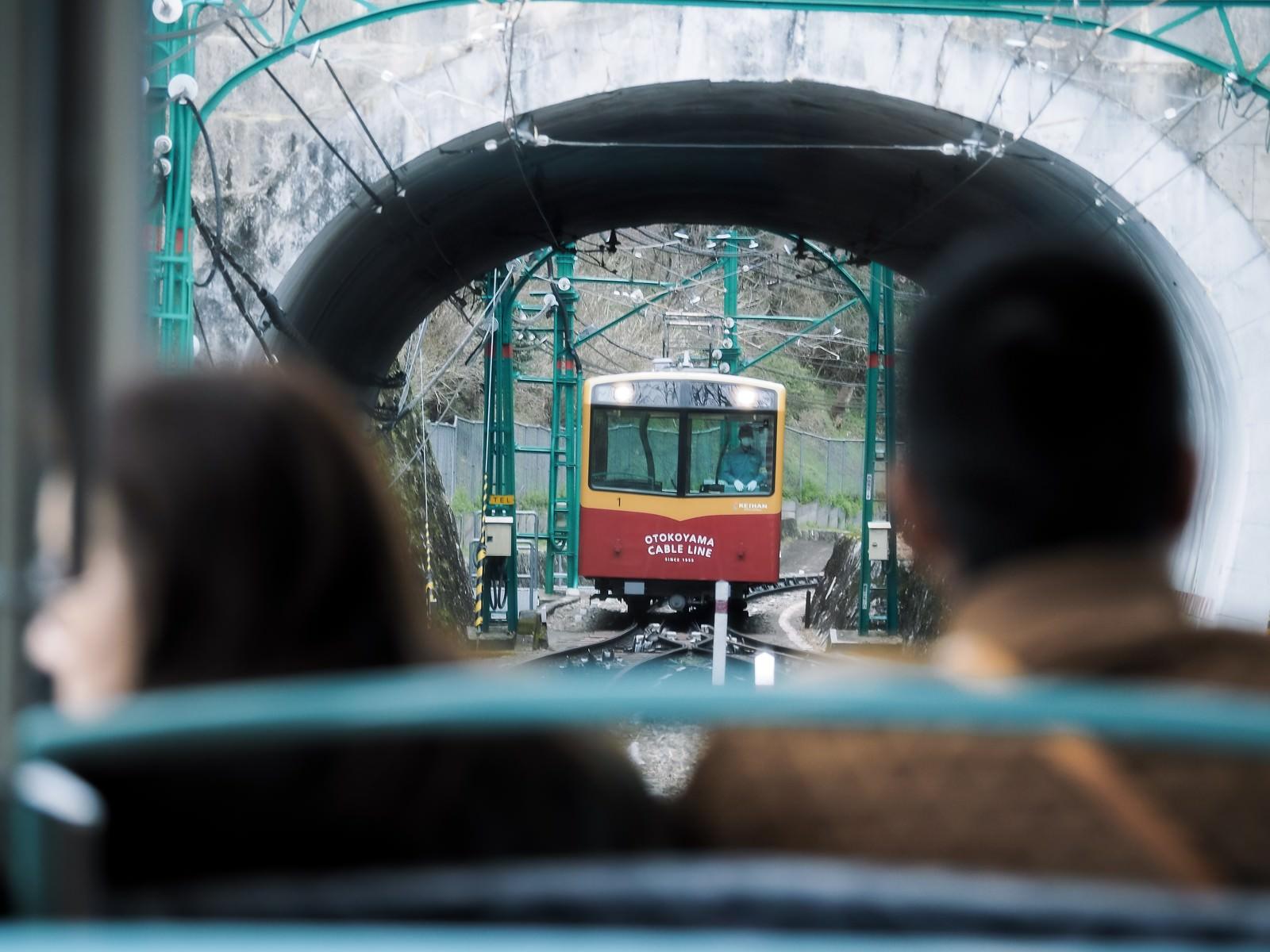 「トンネル越しに見る接近中のケーブルカー(鋼索線客車)」の写真