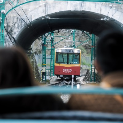 トンネル越しに見る接近中のケーブルカー(鋼索線客車)の写真