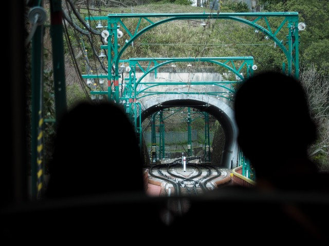 男山ケーブルの乗客越しに見るトンネルの写真