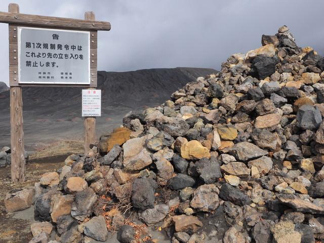 阿蘇山の積まれた岩石と立ち入り禁止の看板の写真