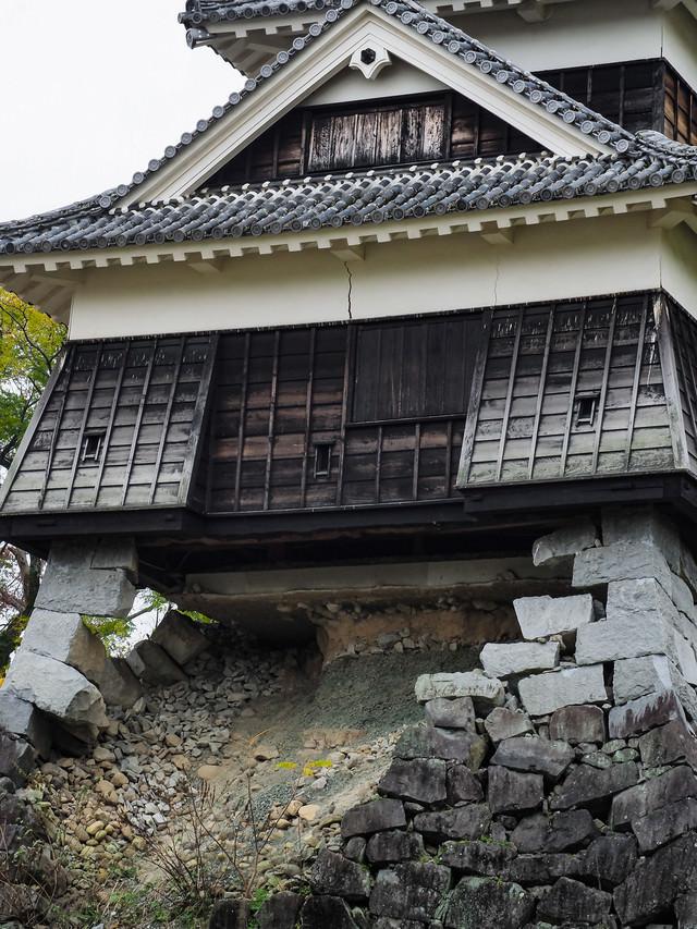 崩れ落ちた石垣と崩れない戌亥櫓(いぬいやぐら)の写真
