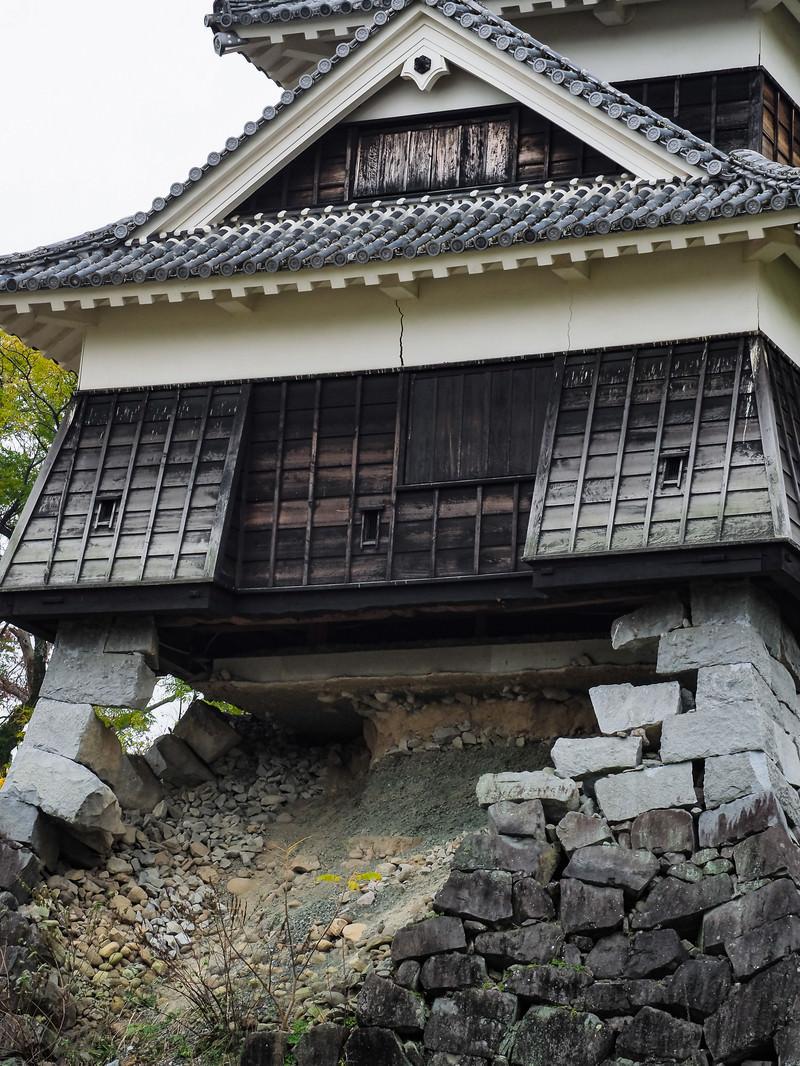 「崩れ落ちた石垣と崩れない戌亥櫓(いぬいやぐら)」の写真