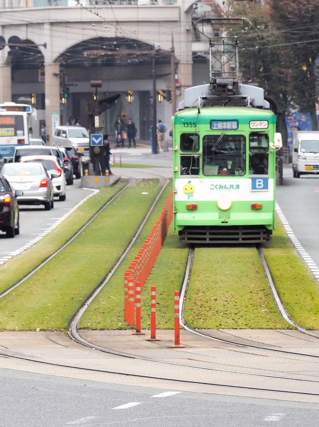 緑化された路線を走る熊本市電(路面電車)の写真