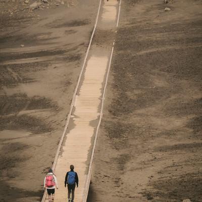 草千里に敷かれた木道を歩く登山者達の写真
