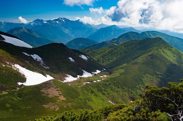 雪が残る山間、乗鞍新登山道から見える景観の写真