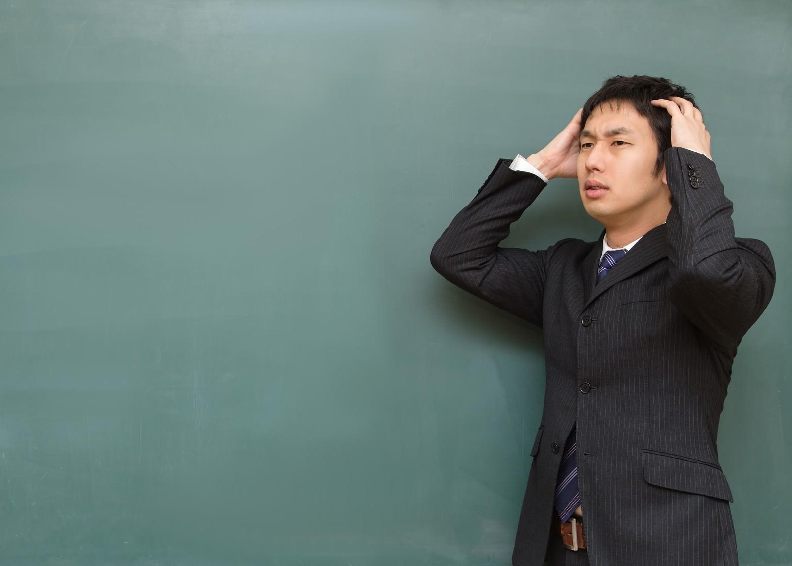 「頭を抱える塾の講師」の写真[モデル:大川竜弥]