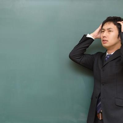 「頭を抱える塾の講師」の写真素材