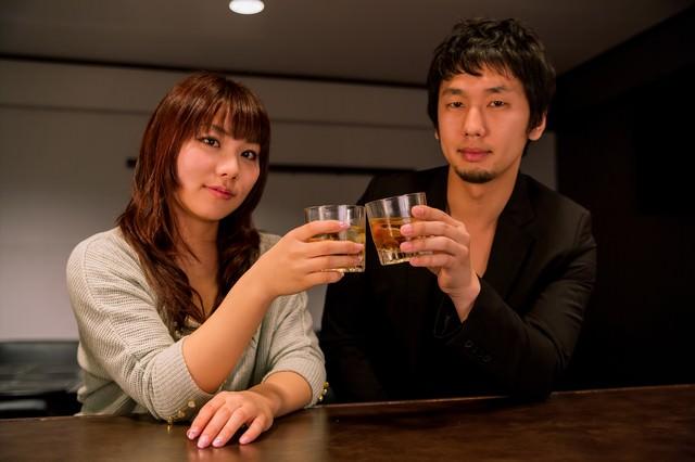 バーカウンターで乾杯する恋人の写真