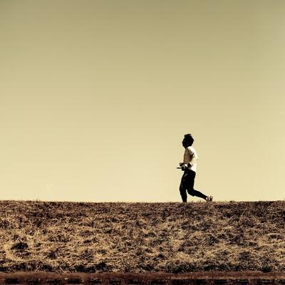 「河川敷を走るランナー(夕暮れ)」の写真素材